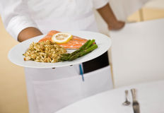 Female waitress offers plate of food Royalty Free Stock Images