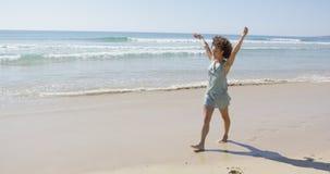 Female walking along the shore of beach Stock Photo