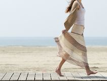 Female walking at the beach barefoot with dress Stock Images