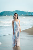 Female walking on beach in summer. Happy multiracial Asian girl going to sea. Female walking on beach in summer. Beautiful happy multiracial Asian girl in white Stock Images