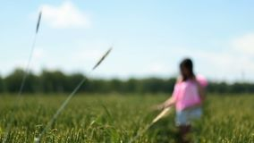 Female walking on a green field touching hair stock video footage