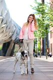Female walking her dog outdoors and talking on mobile phone Royalty Free Stock Photo