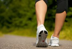 Female walking outdoors in running shoes. From behind Stock Images