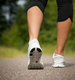 Female walking on path in running shoes. From behind Royalty Free Stock Photography