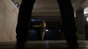 Female walking in underpass watched by criminal. View from between male criminal legs, back view of beautiful young woman walking through dark underpass at night stock footage