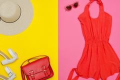 Female wardrobe. Orange overalls, handbag, brown shoes and a hat. Pink and yellow background. Fashion concept Royalty Free Stock Images
