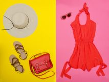 Female wardrobe. Orange overalls, handbag, brown shoes and a hat. Pink and yellow background. Fashion concept Royalty Free Stock Photography
