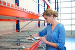Female warehouse employee standing next to shelves and writing on clipboard Stock Image