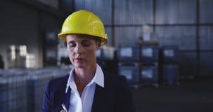 Female warehouse manager checking stock in storeroom 4k
