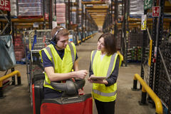 Female warehouse manager instructing man on tow tractor. Female warehouse manager instructing men on tow tractor royalty free stock photos