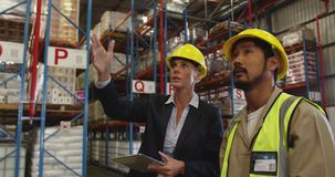 Female warehouse manager and male warehouse worker talking 4k stock footage