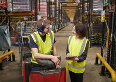 Female warehouse manager and man on tow tractor discuss. Female warehouse manager and men on tow tractor discuss stock image