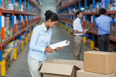 Female warehouse worker with a clipboard checking the boxes. In the warehouse Stock Image
