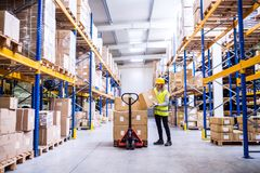 Female warehouse worker loading or unloading boxes. Young female warehouse worker loading up a pallet truck with boxes. A woman unloading boxes stock images