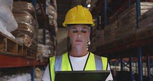 Female warehouse worker patrolling warehouse corridor at night 4k stock video footage