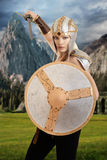 Female warrior attacking with shield and sword. With mountains in background royalty free stock photography