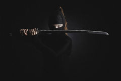 Female warrior. Ninja woman warrior with catana on black background Stock Photography