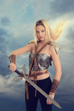 Female warrior with sword and hair blowing in wind. And stormy sky royalty free stock images