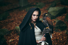 Female warrior with sword and hawk. Cinematic colors royalty free stock photos