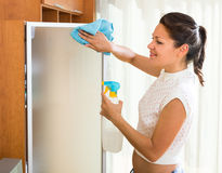 Female washing glass with sprayer. Happy female washing glass with sprayer and rag Stock Image