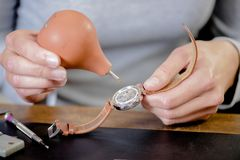 Female watch repair expert. Battery Stock Photography