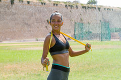 Female water sprinkled athlete in sportswear with mrssuring tape. Female water sprinkled wet athlete woman in sportswear measuring her waistline, hips and chest Stock Image