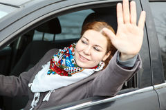 Female waving hers hand from car Stock Photo
