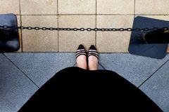 Female Wear Black Dress and Black Shoes Woman Standing on The Tile Background Stock Images