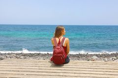 Female wearing backpack and casual outfit resting and relax on the beach in sunny summer day stock image