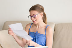 Female wearing casual clothing received positive exam results. Smiling young woman in eyeglasses reading letter on sofa at home happy with good news in written stock image
