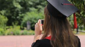 Female wearing graduation cap photographing friends on smartphone in park stock footage