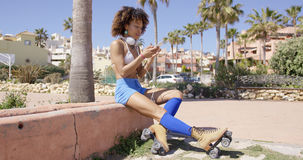 Female wearing rollerskates sitting on curb Stock Images