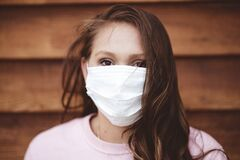 Female wearing a sanitary face mask in front of a wooden wall - Pandemic