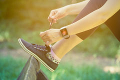 Female wearing smart watch and tying shoelaces in the park. Close up shoot of female tying shoelaces and wearing watchband touchscreen smart watch with blank royalty free stock images