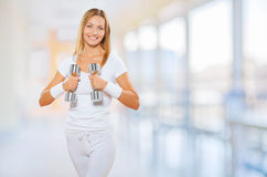 A female wearing sports clothes holding barbells Royalty Free Stock Images
