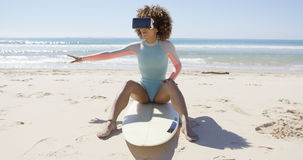 Female wearing virtual reality glasses on beach Stock Photos