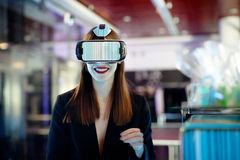 Female wearing virtual reality glasses. Smiling female wearing virtual reality glasses on party background Stock Photography