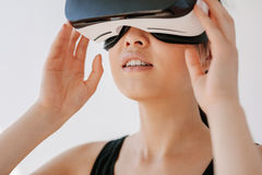 Female wearing virtual reality headset. Close up of happy young woman using the VR goggles against grey background. Asian female model wearing virtual reality royalty free stock photos