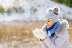 Female wearing warm outfit during winter. Pretty young woman blowing snow playing with it. Female having grey beanie warm hat with pompons and blue scarf royalty free stock image