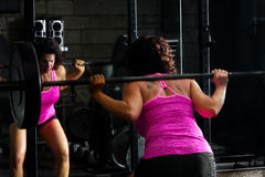 Female Weightlifter Doing Barbell Squats. A strong, female weightlifter does barbell squats with intense concentration. She is wearing a bright pink tank top and Stock Photography