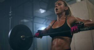 A female weightlifter performs a barbell lift in a dark gym. a woman lifting a heavy bar over her head