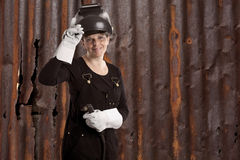 Female welder standing in front of a old rusty metal wall Stock Images