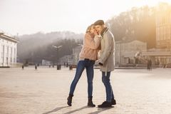 Female is whispering on ear to male something important. Innermost thoughts. Full length of young romantic couple is standing outdoors. Elegant girl in Stock Photos