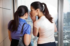 Female Whispering to Co-worker Stock Photo
