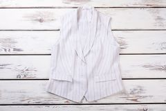 Female white formal vest with black stripes. Women waistcoat on white wooden background. Ladies office outfit Stock Images