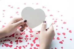 Female with white paper heart shape. On small red hearts background.love, valentine,wedding concepts ideas royalty free stock photo