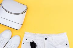 Female white sneakers and jeans on yellow background with copy space. Top view. Summer fashion, shopping, capsule wardrobe concept royalty free stock photos