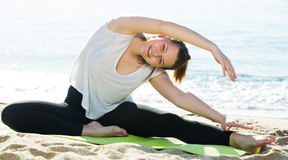 Female in white T-shirt is practicing set of stretching exercise Stock Images