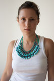 Female in white top and turquoise necklace Stock Photo