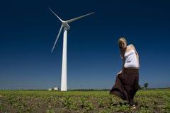 Female at wind power generator. Turbine - alternative and green energy source Stock Image